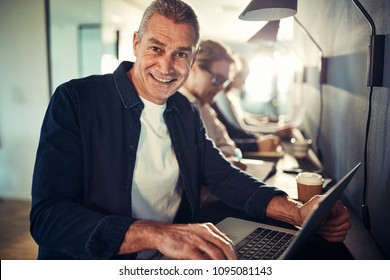 Smiling mature designer working on a laptop while sitting in a row with coworkers at a table in a modern office