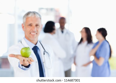 Smiling mature doctor holding an apple