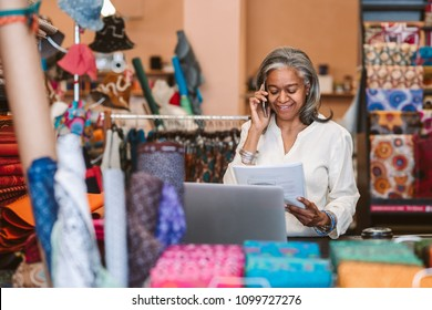 Smiling mature fabric shop owner standing behind a counter surrounded by colorful textiles reading paperwork and talking on a cellphone