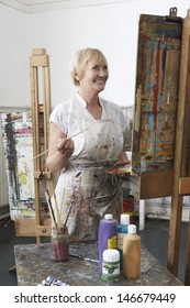 Smiling mature female artist painting at easel in art studio