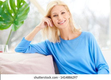 Smiling mature female beauty holding a cup of tea in her hand while sitting on sofa at home.