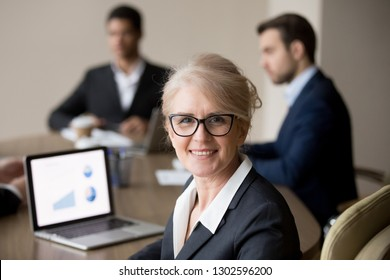 Smiling mature female company executive, professional manager, company ceo looking at camera, happy middle aged businesswoman in glasses posing at team office meeting, woman boss head shot portrait