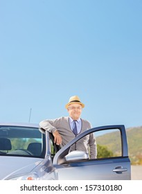 Smiling mature gentleman with hat posing next to his automobile on an open road, shot with a tilt and shift lens