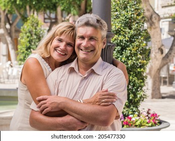 Smiling mature healthy romantic middle-aged couple posing in a close affectionate embrace for a portrait in a town square