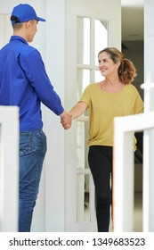 Smiling mature housewife opening the door of her house and greeting serviceman with handshake