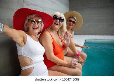 Smiling mature ladies having fun around the swimming pool stock photo