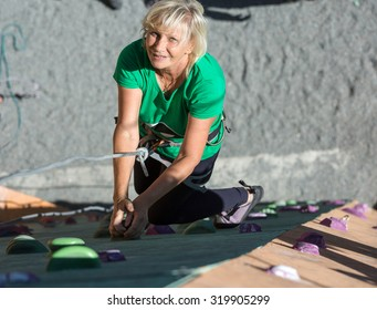 Smiling Mature Lady on Extreme Climbing Wall Portrait of Adult Female Climber Moving Up on Sport Training Course in Outdoor Climb Gym Using Rope and Belaying Gear
