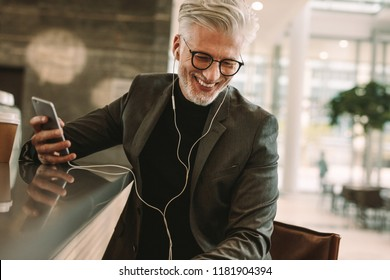 Smiling mature male in business suit sitting at cafe in earphones and holding a mobile phone. Business man making phone call using earphones in coffee shop.