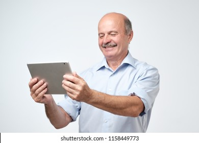 Smiling mature male using digital tablet against gray background. Find needed information in web. Study to use internet in old age