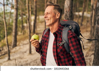 Smiling mature male is walking with backpack in forest and having green fresh apple on way