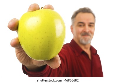A smiling, mature man with a beard holds out an apple for all to see.