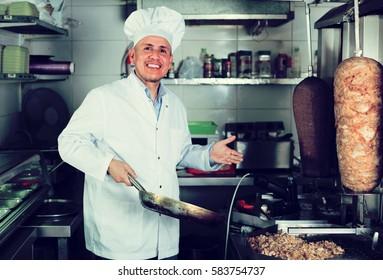 smiling mature man chef in uniform preparing fresh kebab in restaurant