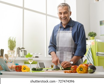 Smiling mature man cooking in the kitchen at home, he is wearing an apron and slicing fresh vegetables, healthy lifestyle concept