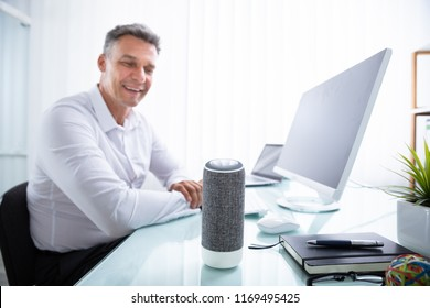 Smiling Mature Man Listening To Music On Wireless Speaker