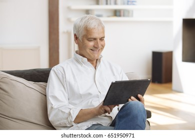 Smiling mature man sitting on a sofa using a tablet pc  in a living room