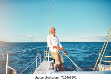 Smiling mature man standing on his boat deck while out for a sail along the coast on a sunny day