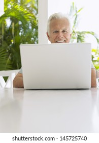 Smiling mature man using laptop at verandah table