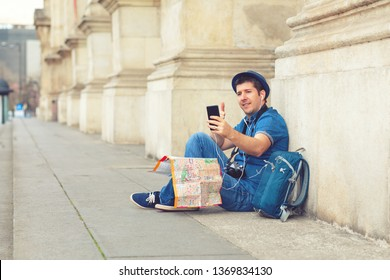 Smiling mature man using mobile phone while sitting against building column – happy tourist taking selfie with smartphone – traveler with backpack and hat showing thumb up on social media