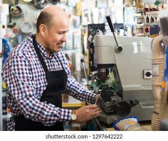 Smiling mature man working in locksmith and making duplicates of keys