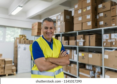 Smiling mature man working in a warehouse. Smiling warehouse worker in uniform in front of camera. Man with clipboard in reflective safety vest at warehouse
