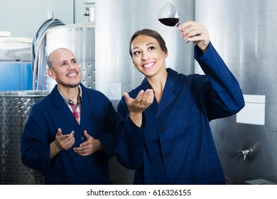 Smiling mature man and young women coworkers looking at wine in glass at factory