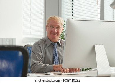 Smiling mature marketing specialist at his workplace