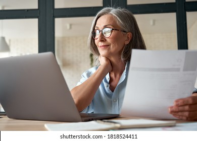 Smiling mature middle aged business woman using laptop working on computer sitting at desk. Happy old businesswoman hr holding cv interviewing distance applicant, senior seeker searching job online. - Shutterstock ID 1818524411