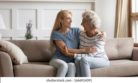 Smiling mature mother and grownup daughter sit relax on couch in living room talking and chatting, happy senior mom and adult girl child rest on sofa at home, enjoy family weekend bonding together