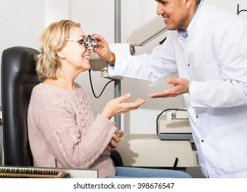smiling mature optician examinating eyesight with aid of slit lamp