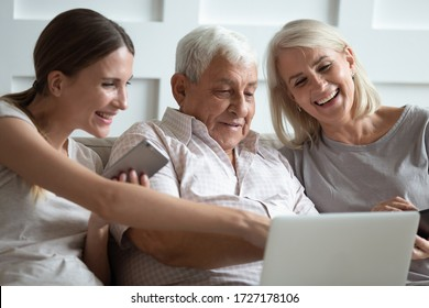 Smiling mature parents sit relax on couch with grownup daughter using modern laptop gadget together, happy senior mom and dad rest have fun watch video with adult millennial girl on computer