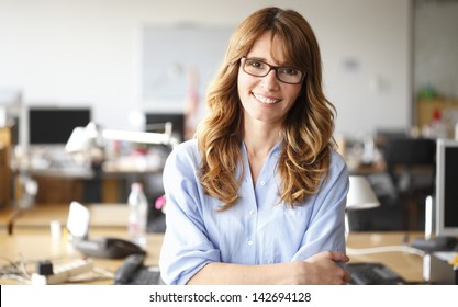 Smiling mature professional businesswoman in casual, with arms crossed standing in office. Shallow focus.