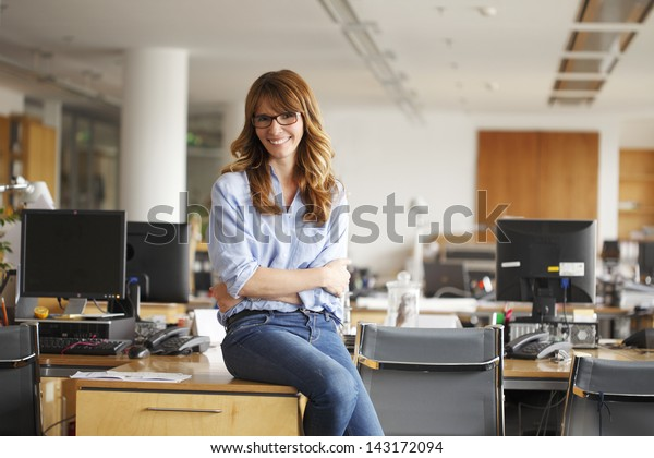 Smiling mature professional businesswoman in casual, with arms crossed sitting on the desk in office. Shallow focus.