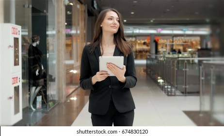 Smiling mature professional businesswoman in office. Holding a digital tablet . Woman brunette in airport or shopping mall