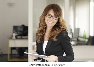 Smiling mature professional businesswoman standing in office. Holding a digital tablet . Shallow focus.