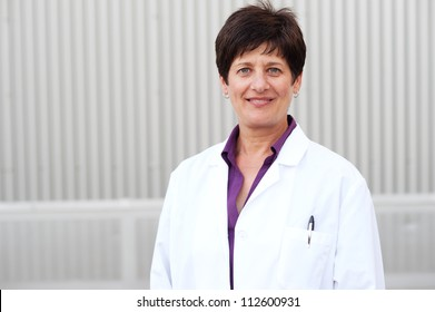 Smiling mature professional woman dressed in labcoat standing outside