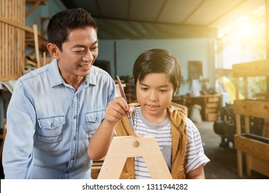 Smiling mature Vietnamese man proudly looking at his son applying finishing coat of laquer on wooden furniture detail
