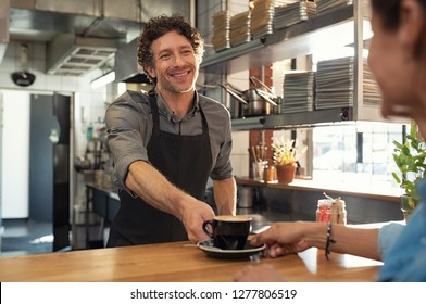 Smiling mature waiter giving hot coffee to woman at cafeteria. Happy man standing behind counter giving a cappuccino to woman in a coffee shop. Portrait of cheerful man serving customer at restaurant.