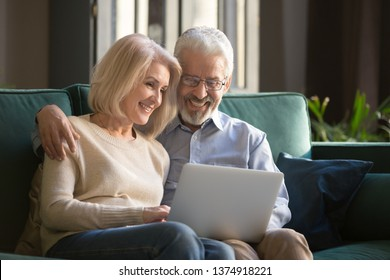 Smiling mature wife and husband, family using laptop together at home, sitting on cozy sofa, aged couple relaxing, watching video or shopping online, looking at screen, elderly and technology concept