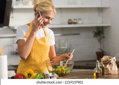 smiling mature woman in apron talking by smartphone while cooking in kitchen