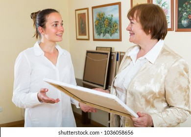 Smiling mature woman and art consultant choosing picture at the gallery