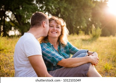Smiling mature woman being kissed by her beloved son