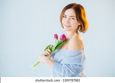 Smiling mature woman in blue sweater holding bouquet of tulips ower blue gray background. Portrait of smiling happy shining senior woman with flowers looking at camera.
