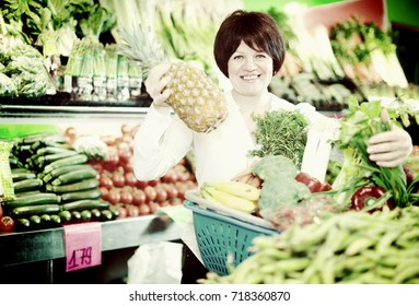 Smiling mature woman buying fresh fruits with basket on the market