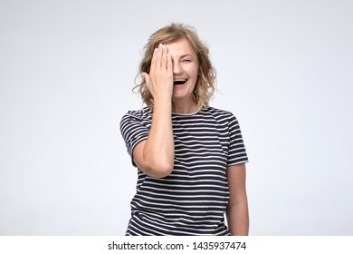 Smiling mature woman covering one eye with hand checking eyesight. She is happy that everything is ok. Human facial positive emotion. Studio shot