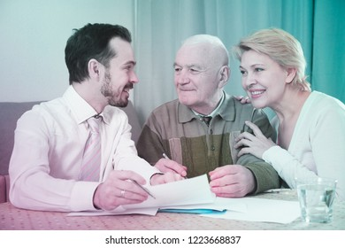 Smiling mature woman and eldery man signing contract with sales manager at home