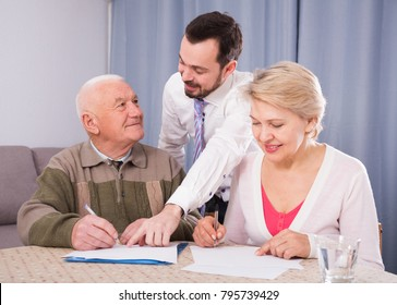 Smiling mature woman and eldery man signing agreement with credit manager at home