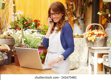 Smiling Mature Woman Florist Small Business Flower Shop Owner.  She is using her telephone and laptop to take orders for her store. Shallow Focus.