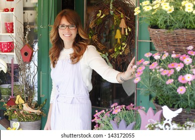 Smiling Mature Woman Florist Small Business Flower Shop Owner standing in front of her shop. Shallow Focus.