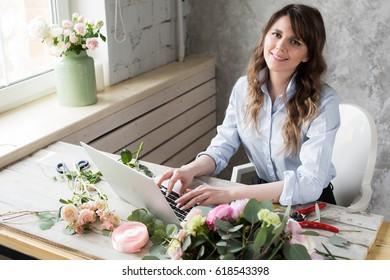 Smiling Mature Woman Florist Small Business Flower Shop Owner. She is using her telephone and laptop to take orders for her store. selective Focus