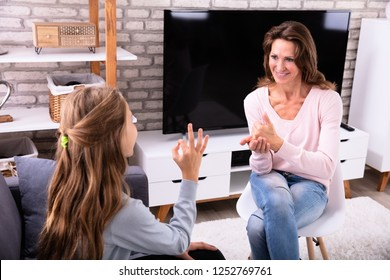 Smiling Mature Woman And Girl Making Sign Languages At Home